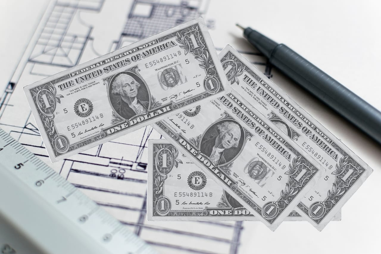money-and-construction-blueprints